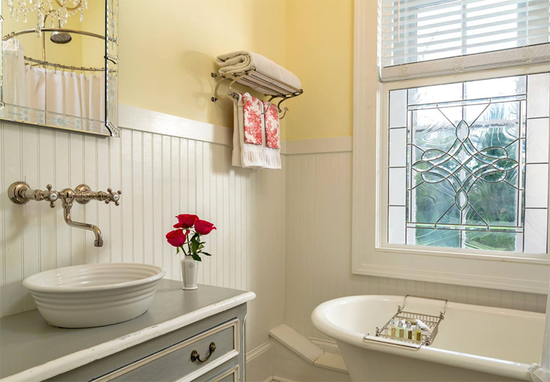 A yellow bathroom features a tub before the window.