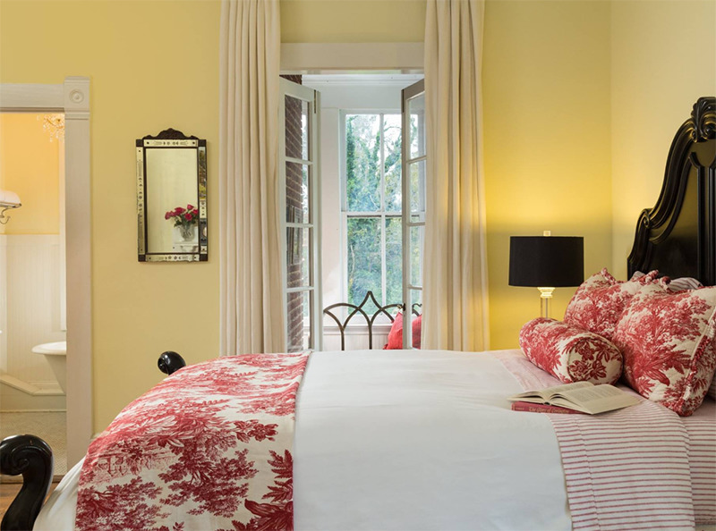 A bedroom has yellow walls and a view of the trees.