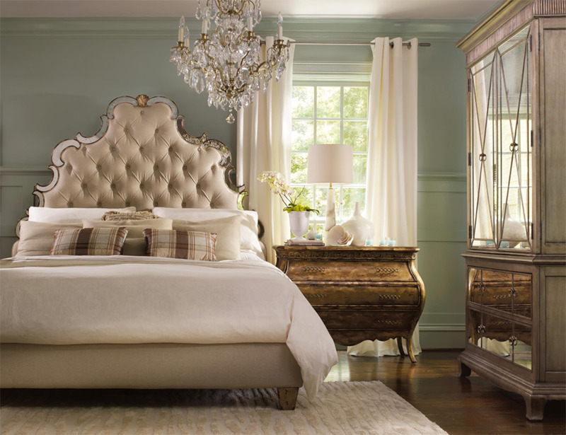 A bedroom features bronze and glass furniture and a chandelier.
