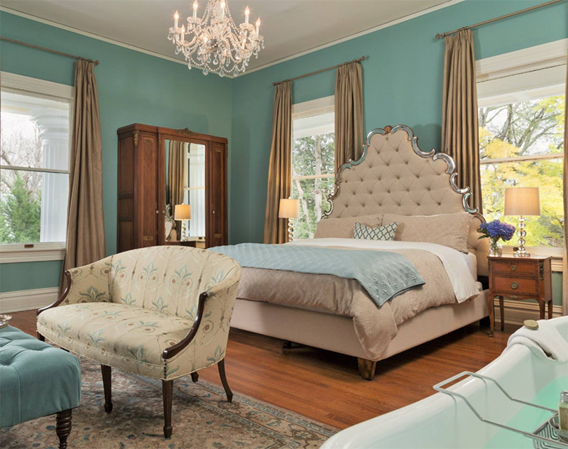 A tub sits in a teal room with a seating area and large bed.