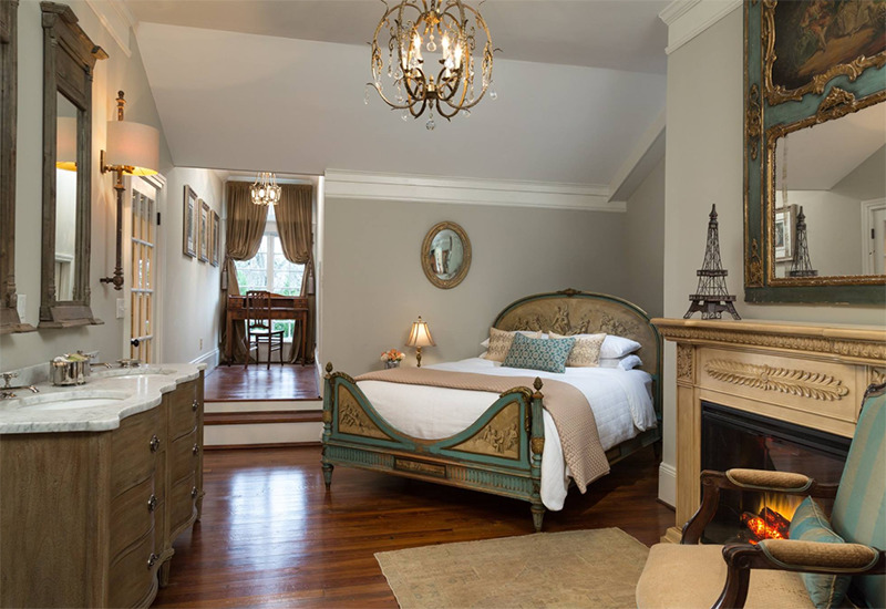 A bed is angeled in a room bedside a fireplace and twin sinks.
