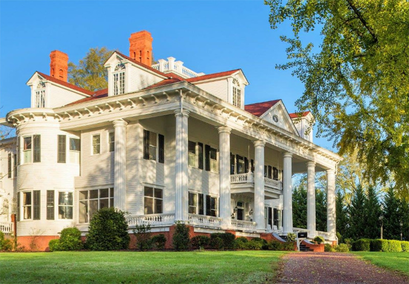 A white, antebellum mansion is surrounded by trees.