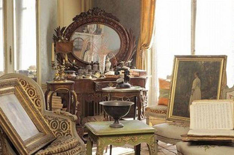 Furniture and paintings are piled up in front of a vanity.