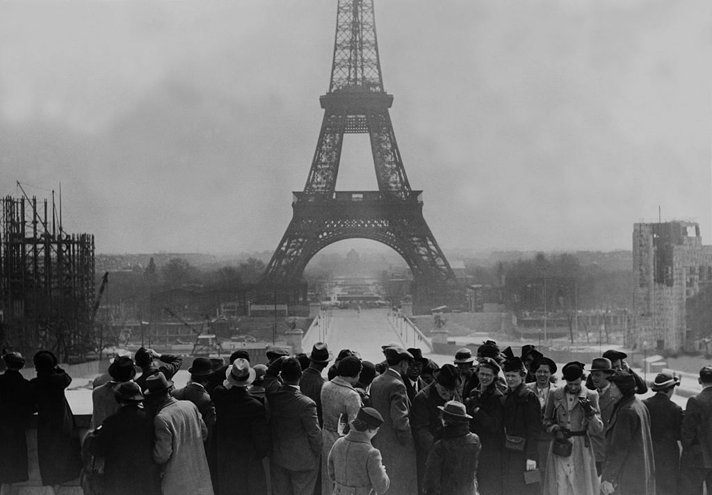 A crowd of people gather in front of the Eifel Tower in the 1930s.