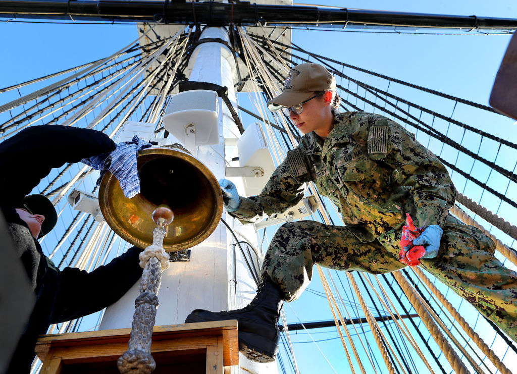 Navy officers polish the bell on the USS Constitution.