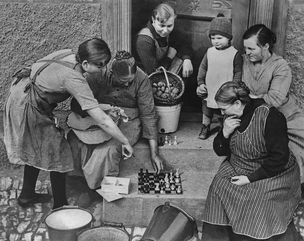 Housewives gather to play a game of chess on a doorstep.