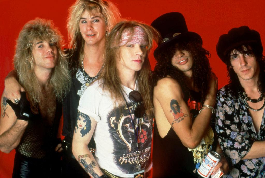 Guns N' Roses posing behind a red background