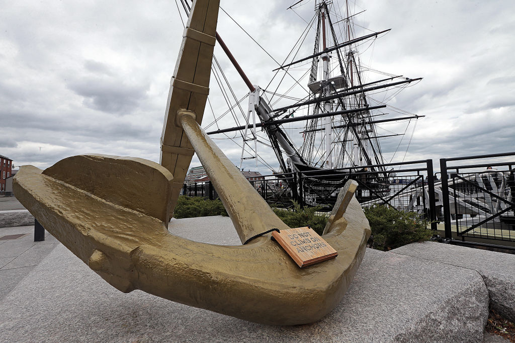 A statue of an anchor stands before the USS Constitution.