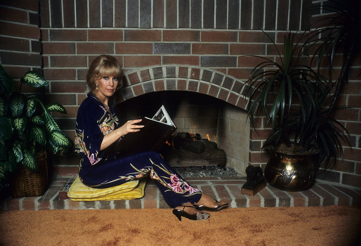 Actress Barbara Eden poses in front of a fireplace c.1985