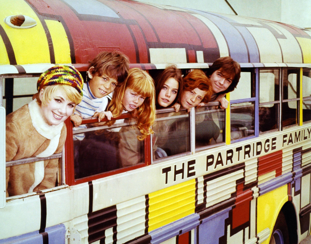 Actors of The Partridge Family lean out of the windows of their bus.
