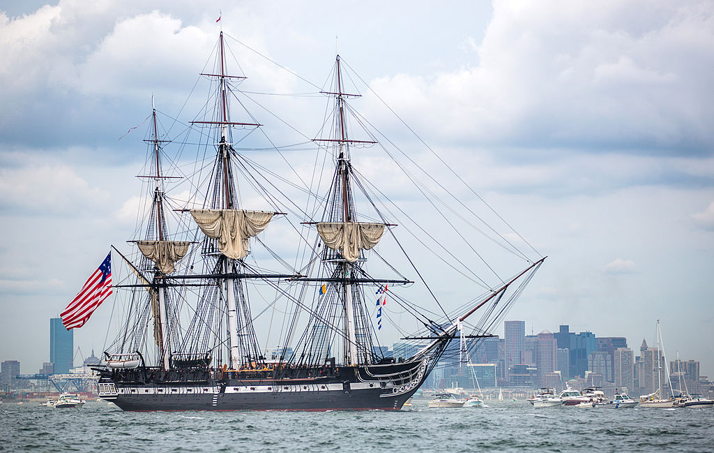 The USS Constitution sales past an urban setting.
