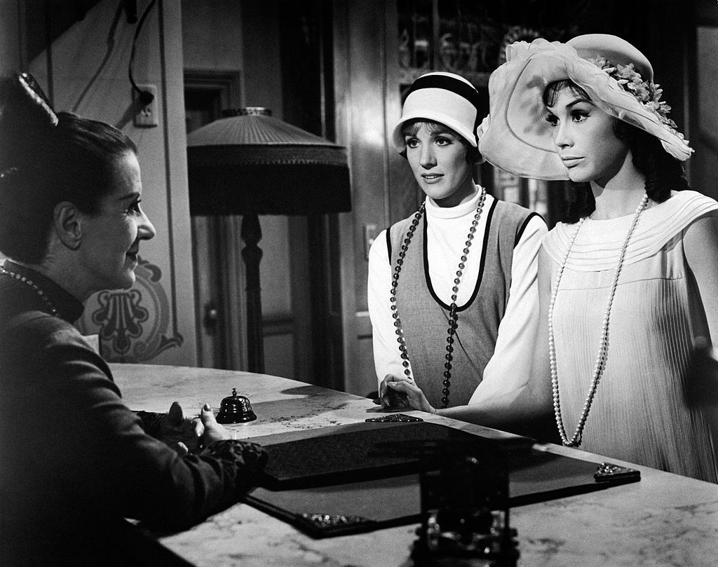 Julie Andrews and Mary Tyler Moore stand at a reception desk performing a scene in a movie.