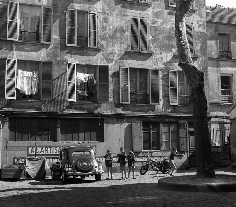 Children play in front of a Paris apartment building in 1935.
