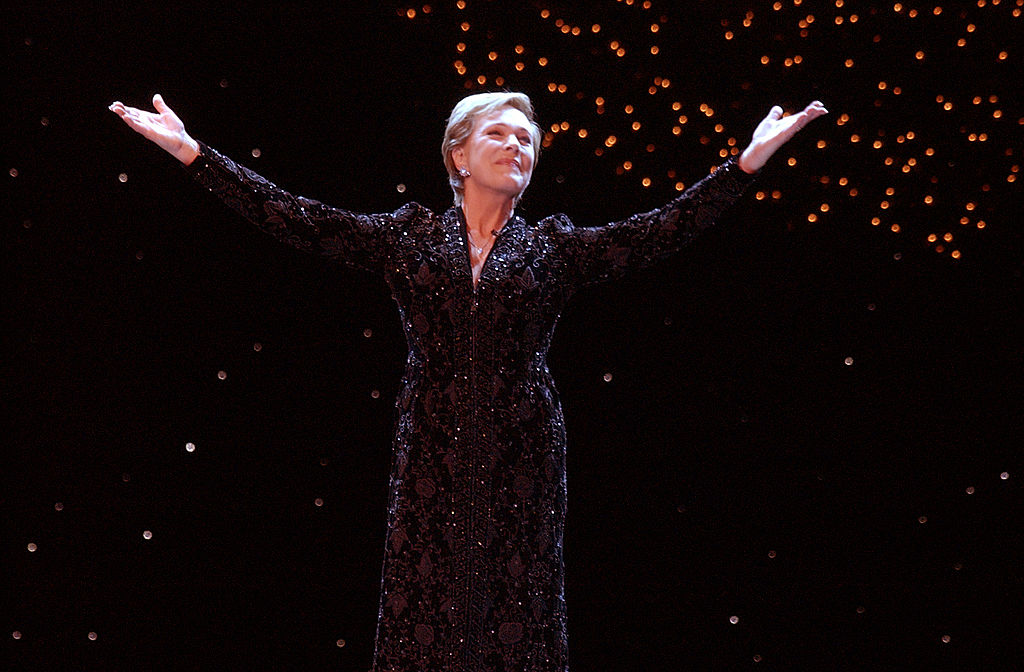 Julie Andrews spreads her arms while onstage during a Christmas performance.