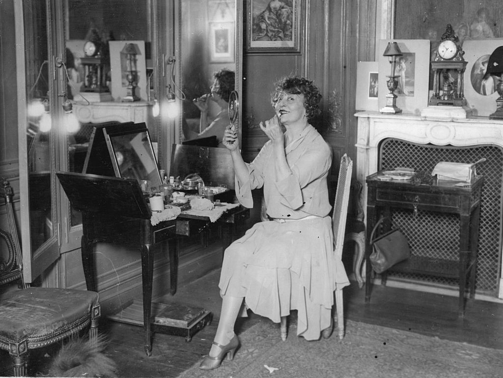 Actress Cicel Sorel gazes at the camera while putting on lipstick at her vanity.