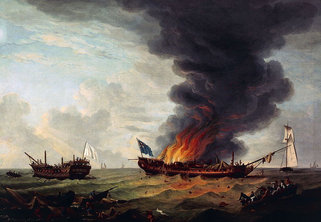 A frigate burns at sea.