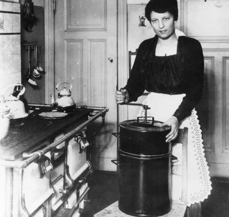 A woman stands in the kitchen cranking an appliance.