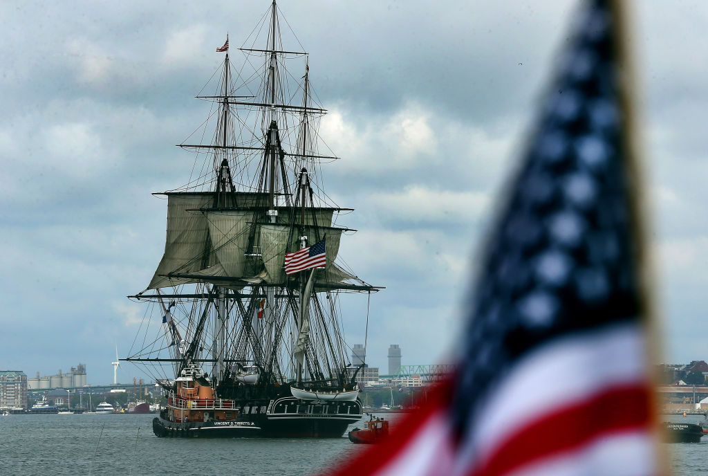 The USS Constitution sails in front of the American flag.
