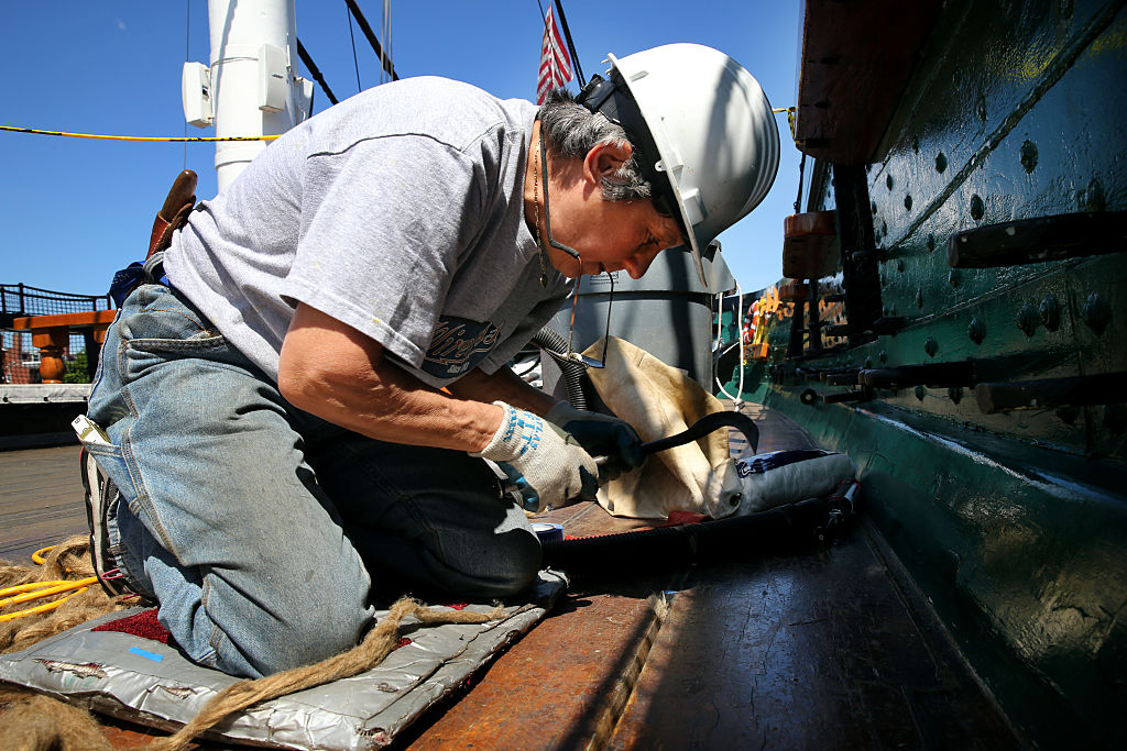 A worker performs repairs on the USS Constitutional.