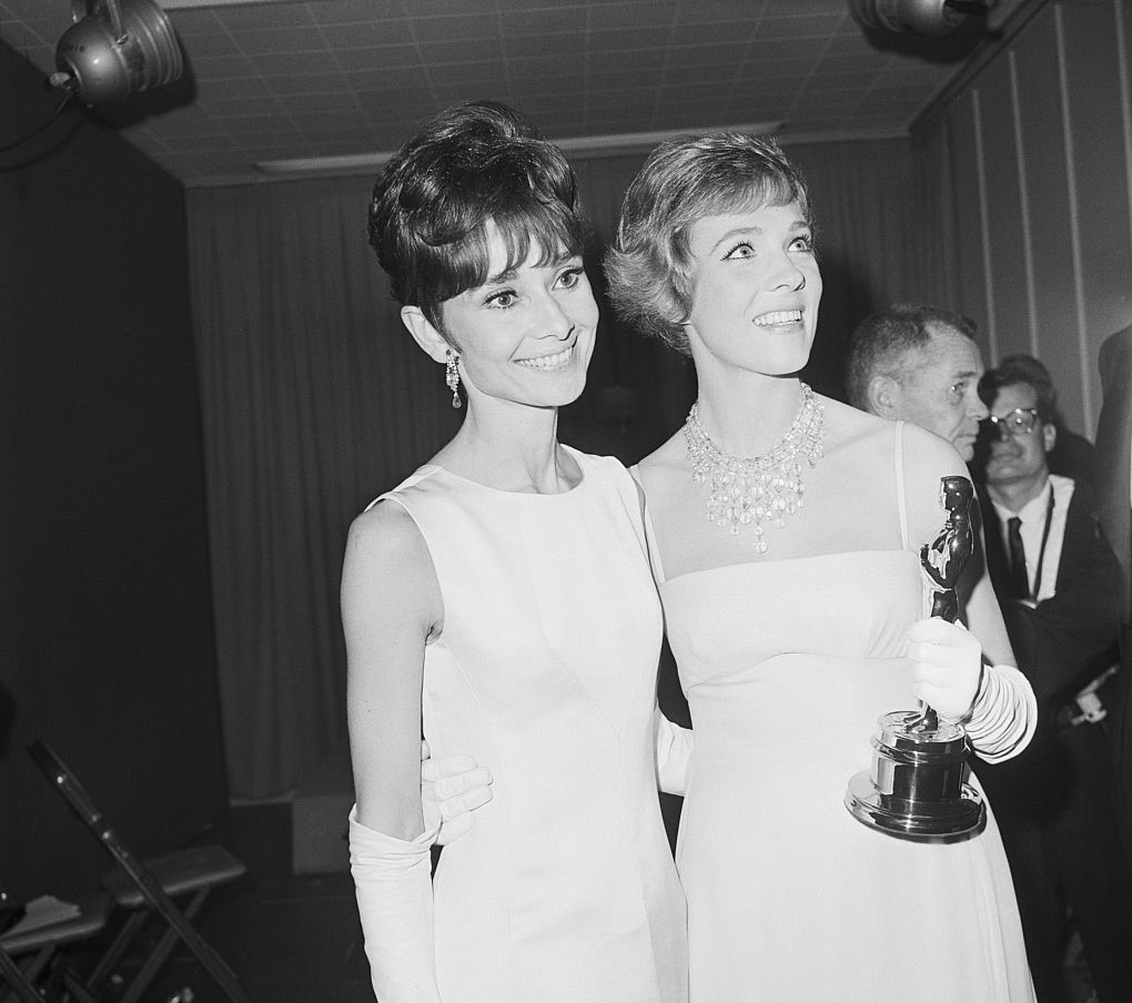 Andrews holds an Academy Award while posing next to Audrey Hepburn.