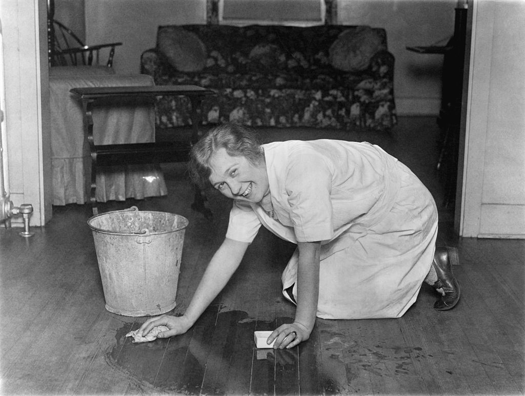 A woman cleans wooden floors on her hands and knees.