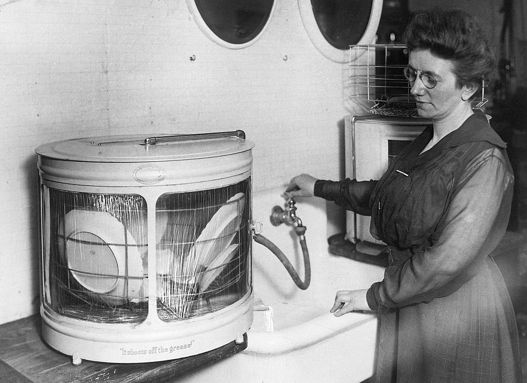 A woman watches as a dishwasher cleans on the counter.