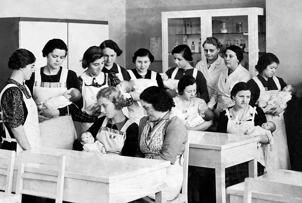 Women hold dolls in a childrearing class.
