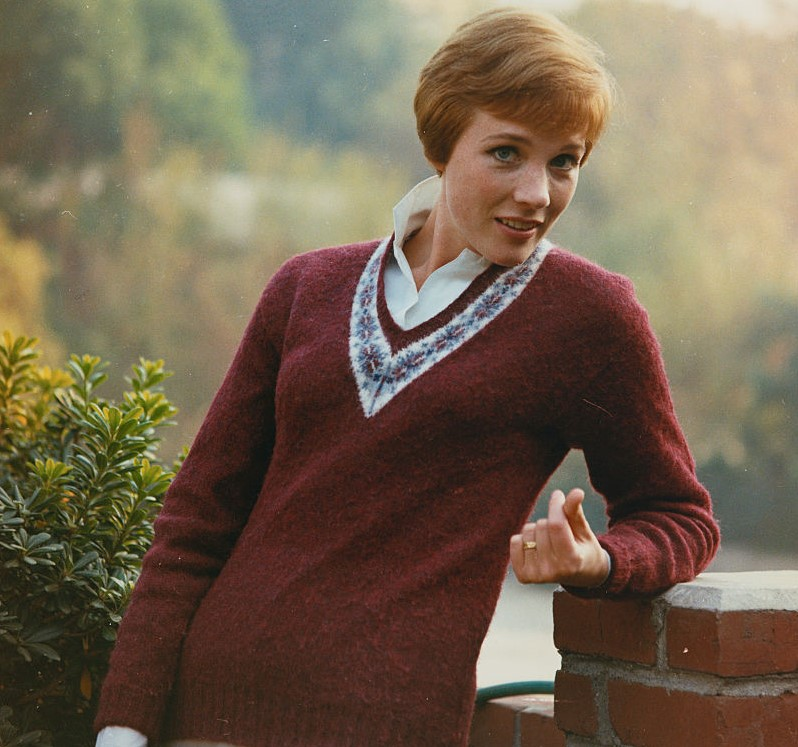 Julie Andrews poses against an open landscape.
