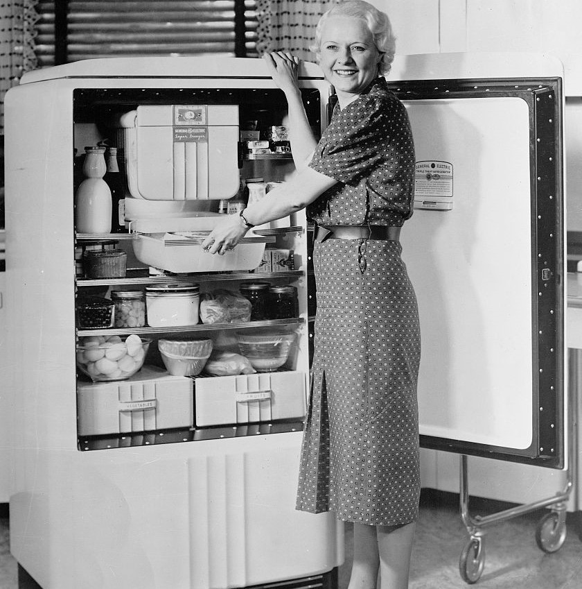 A woman smiles in front of an opened fridge.