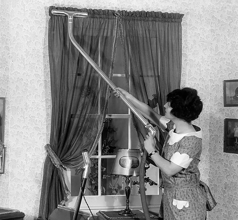 A woman uses an extended vacuum to clean the curtains.