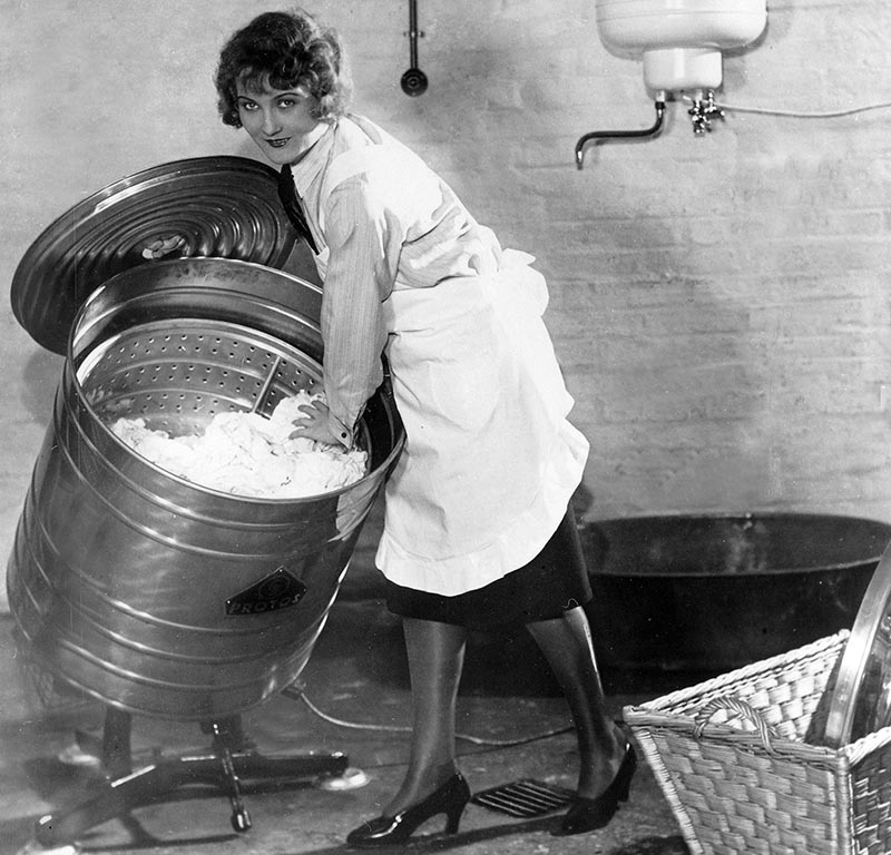 A woman tilts her washing machine.