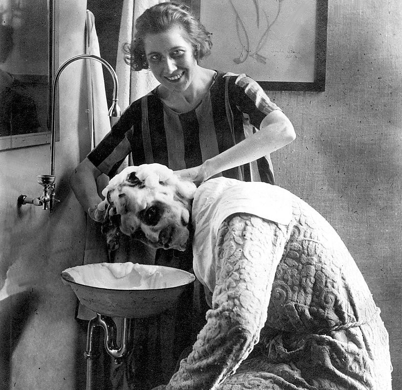 A woman smiles while scrubbing her husband's head in the sink.
