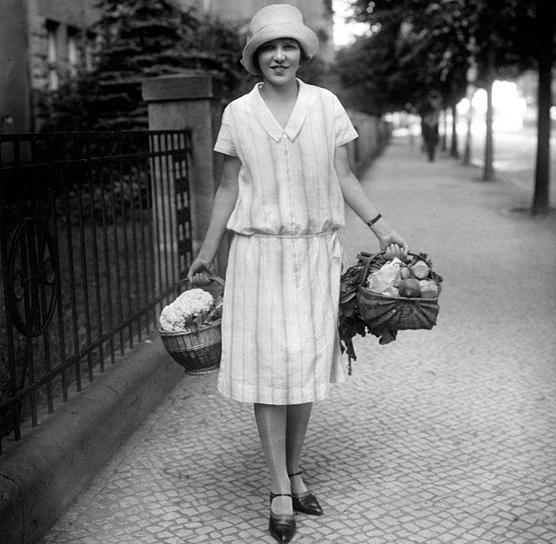 A women walks along the sidewalk with a grocery basket in each hand.