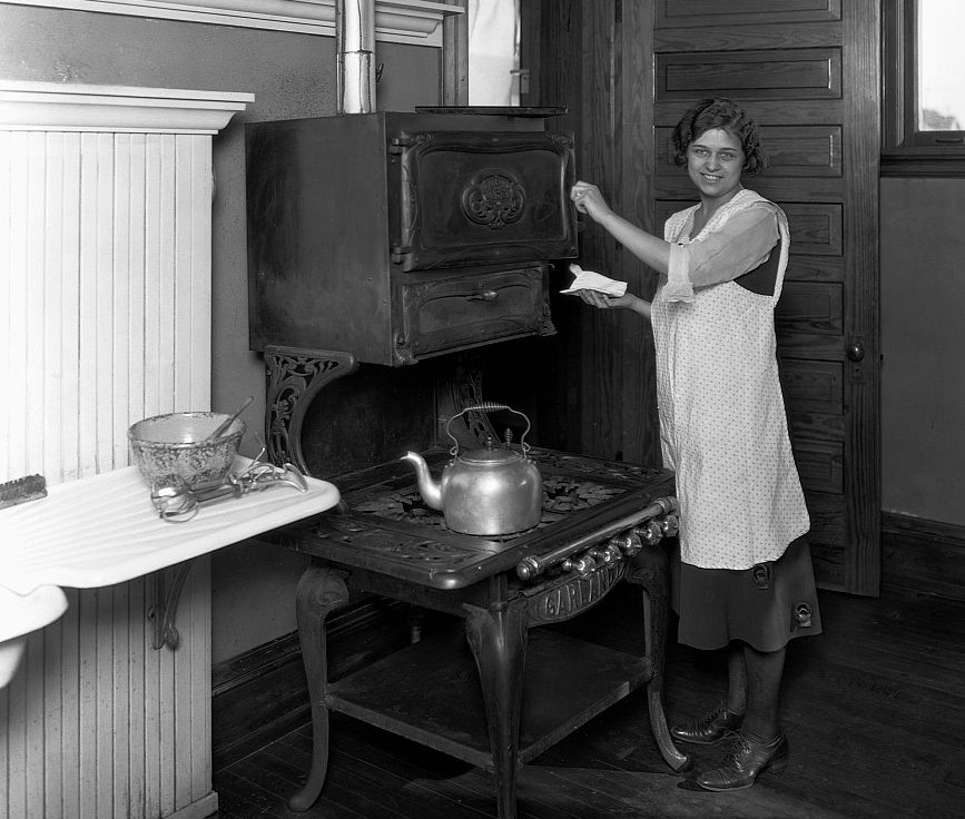 A woman smiles in front of a 1920s stove.
