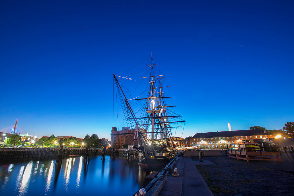 Surrounding lights illuminate the USS Constitution as it's docked at night.