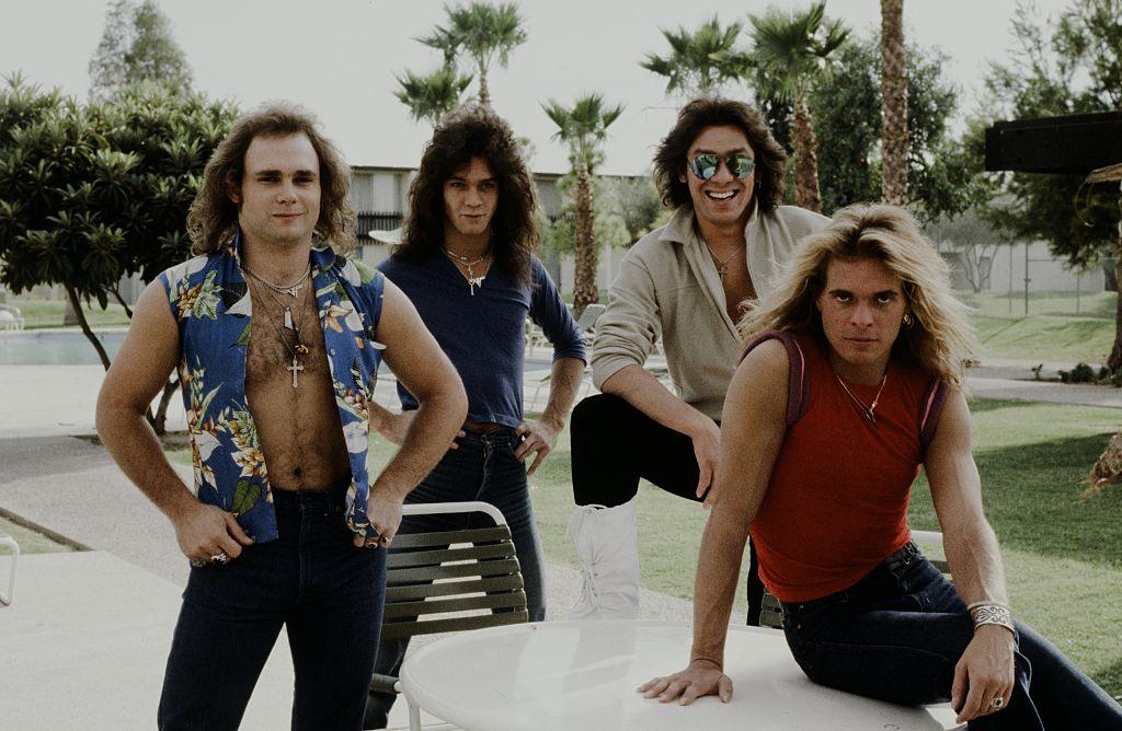 Van Halen posing on a car