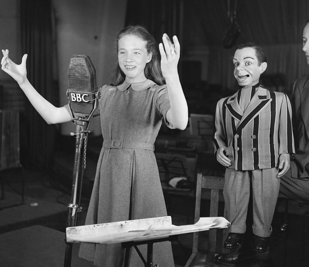 Young Julie Andrews stands in front of a microphone with her arms raised.