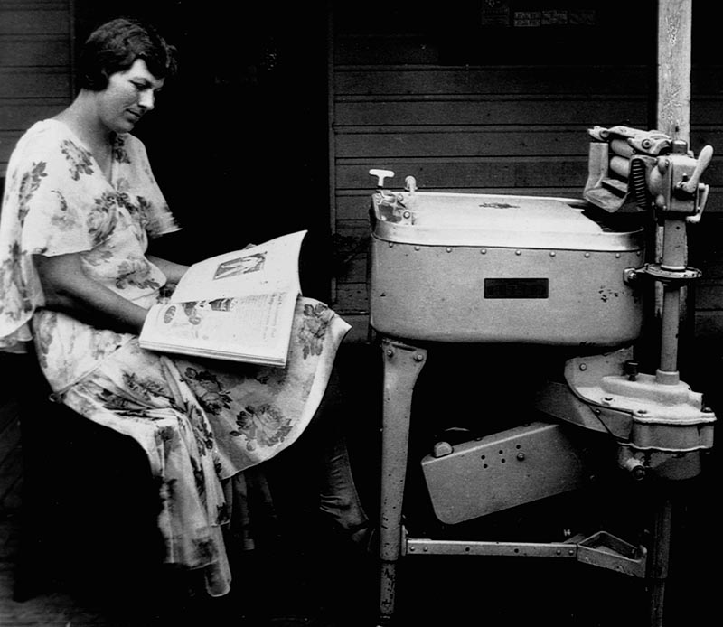 A woman reads while pumping her washing machine.