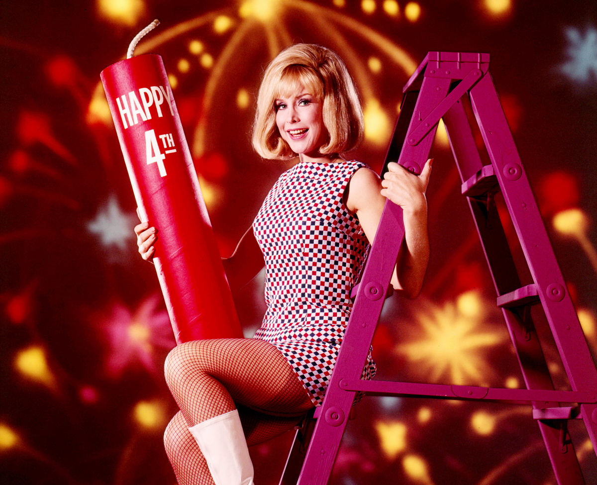 American actress Barbara Eden celebrates the fourth of July up a purple stepladder with a giant firecracker.