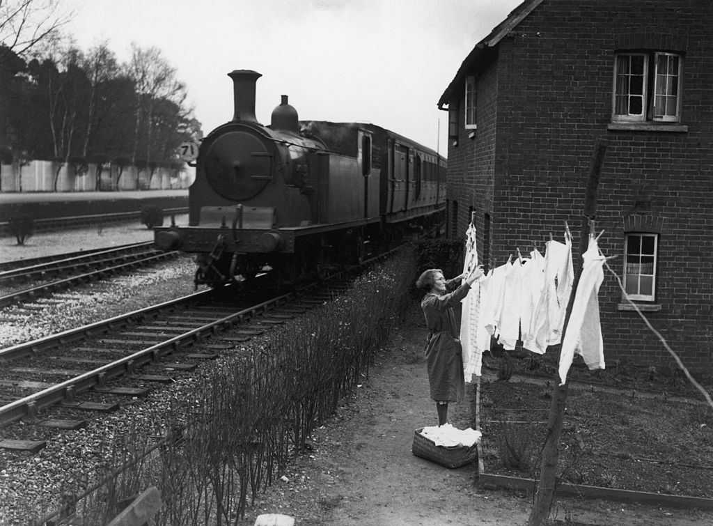 A woman hangs clothes on a line near a passing train.