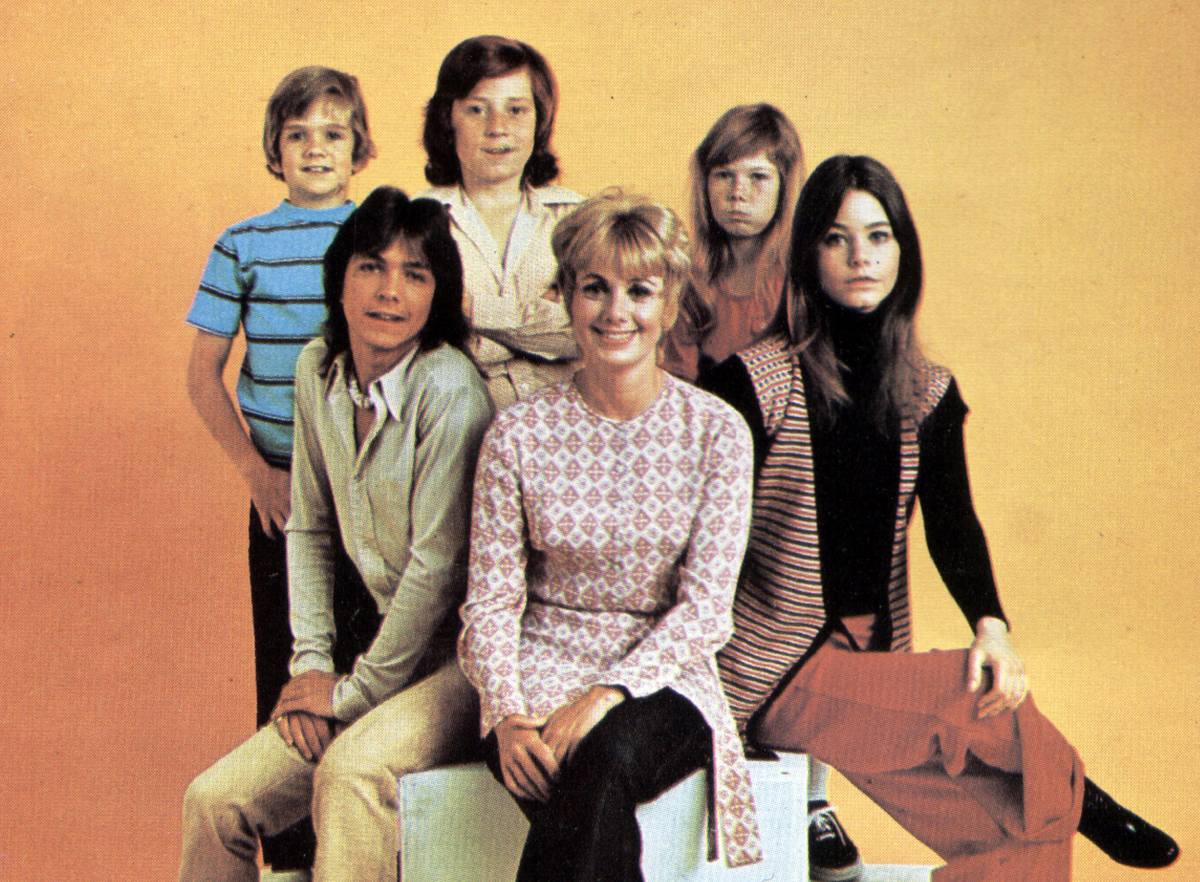 Photo of the Partridge family against a yellow background, circa 1972.
