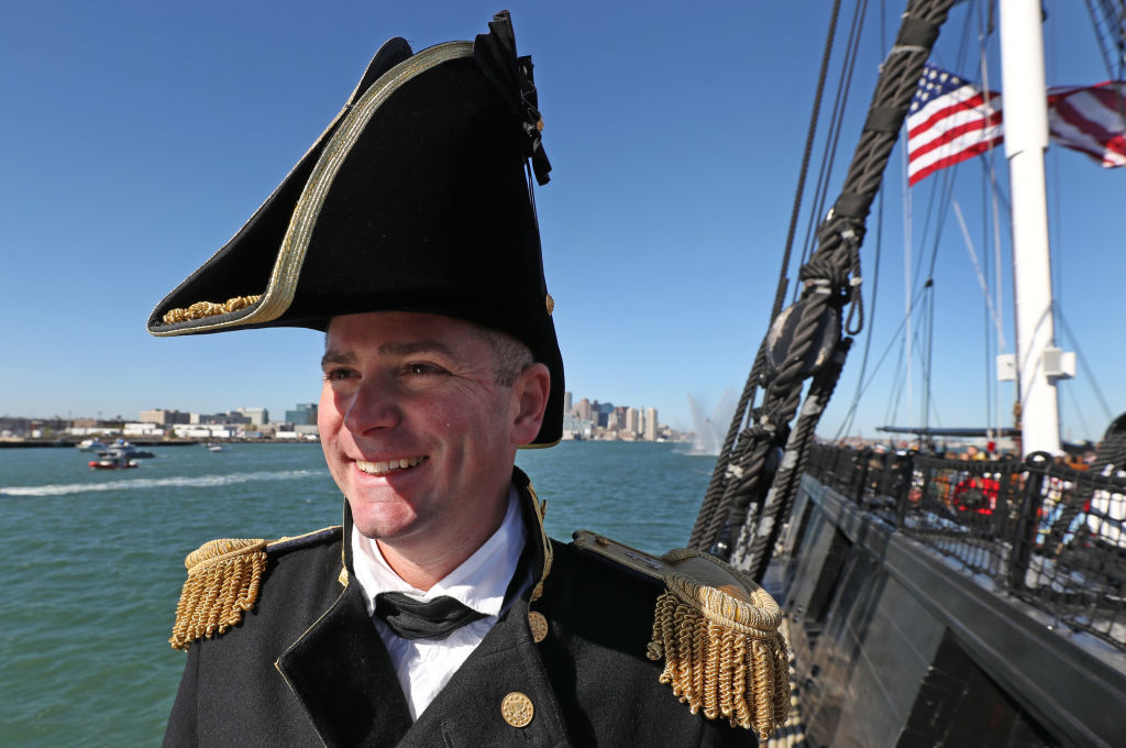 A captain smiles near the USS Constitution.