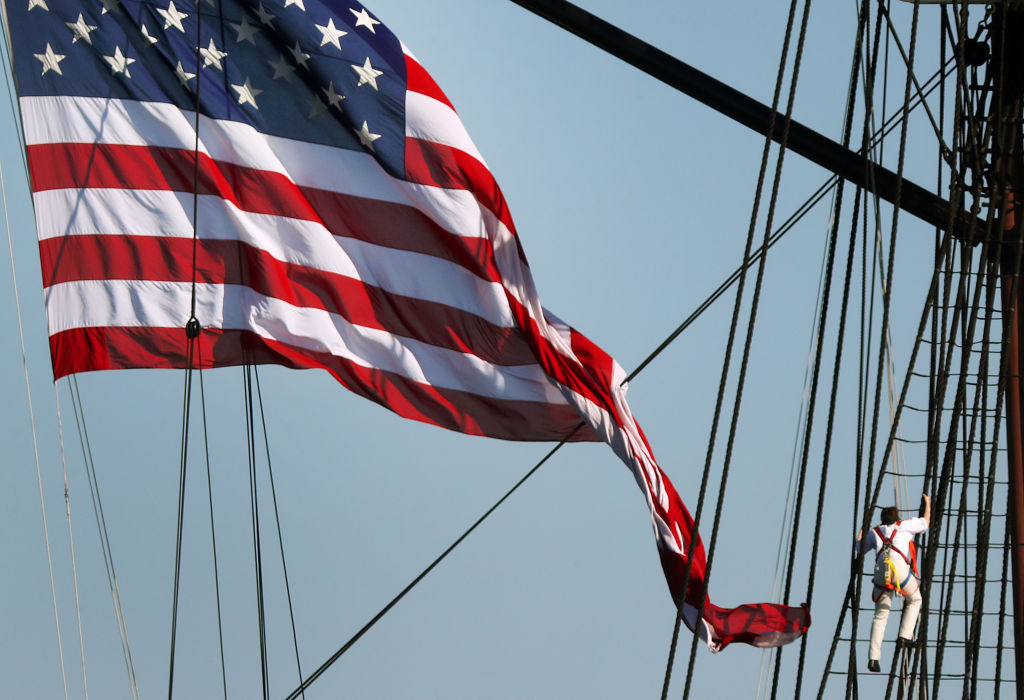 A sailor climbs the mast of the USS Constitution as an American flag waves.