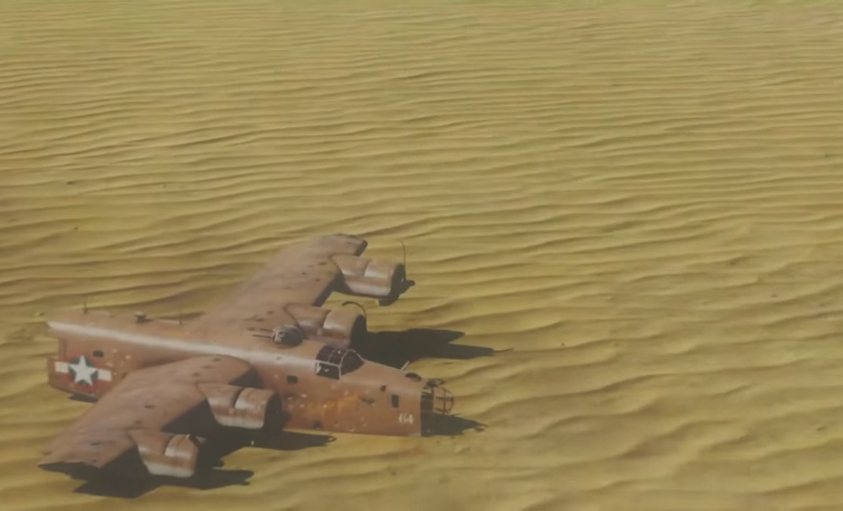 A recreation of the Lady Be Good crash is seen on the desert sand.