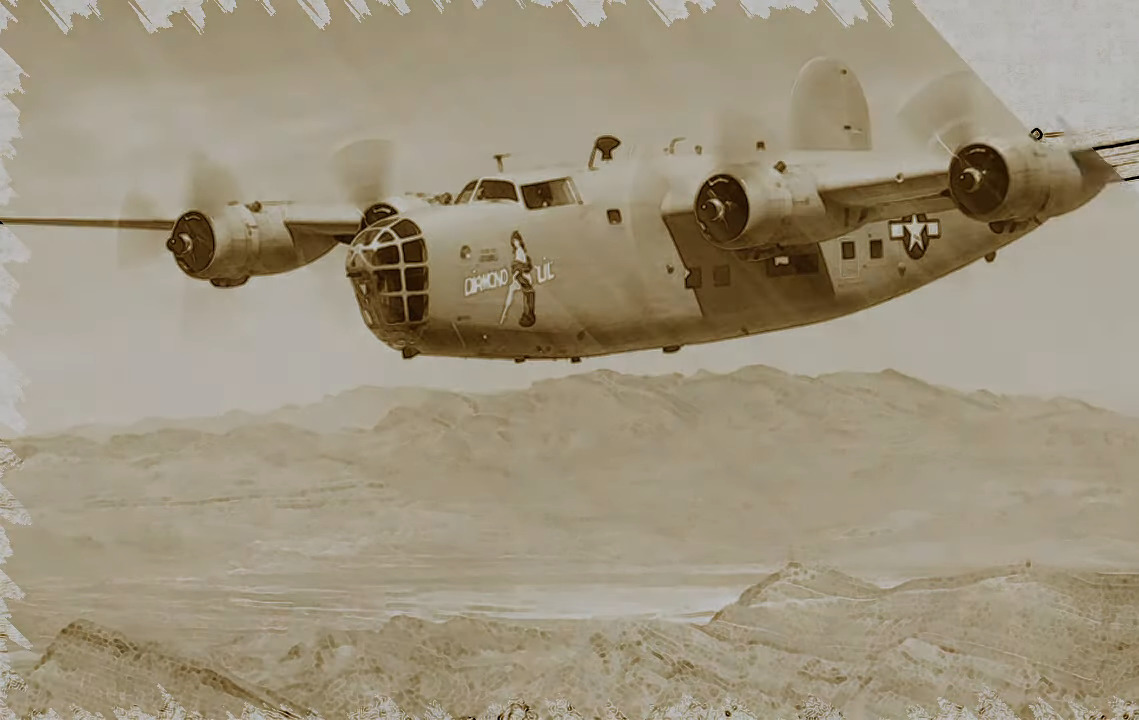 An old B-24 plane flies in front of the mountains.
