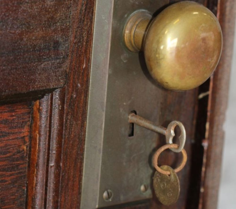 A vintage key is placed into the original door lock.