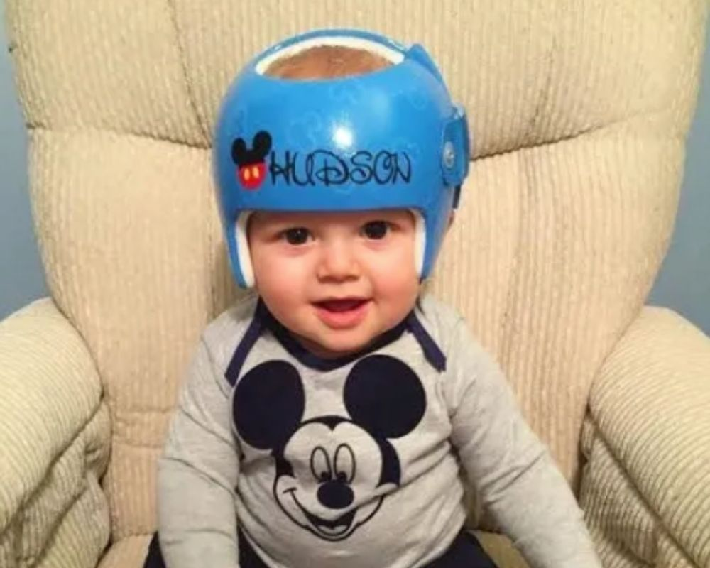Baby boy with helmet that spells his name in Disney font