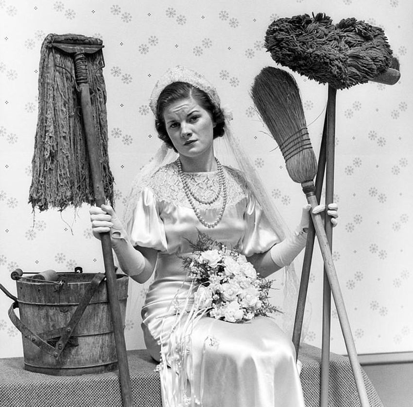 A woman in a bridal gown carries cleaning supplies and looks distraught.