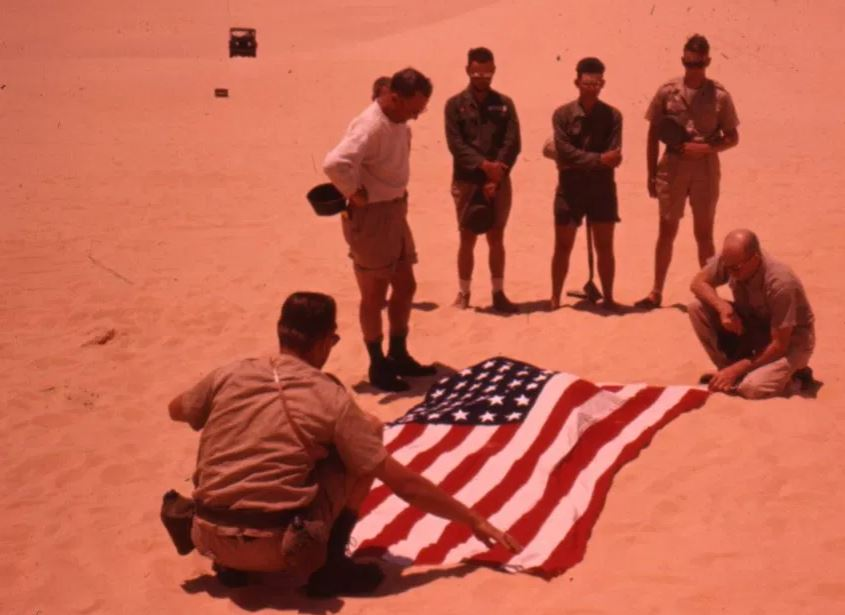 Men who found one of Lady Be Gone's crew members cover the skeleton with an American flag.