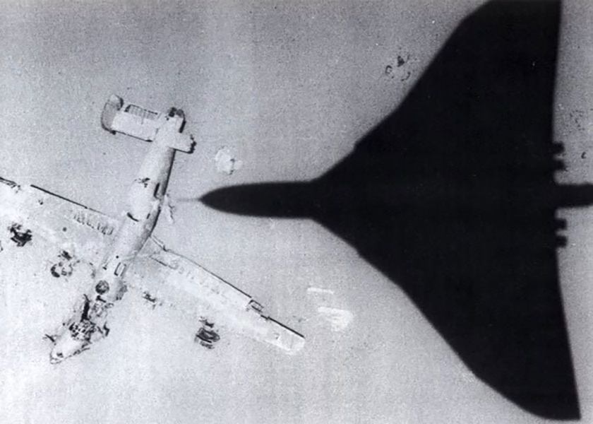 A plane flies over the crashed Lady Be Gone B-24D.